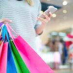 Femeie care urmărește pe telefon mesajele promoționale venite din partea unei companii de retail.