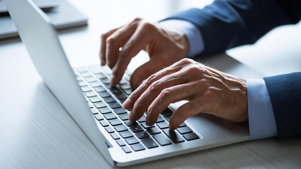 Bărbat la laptop care pregătește lansarea campaniei prin SMS