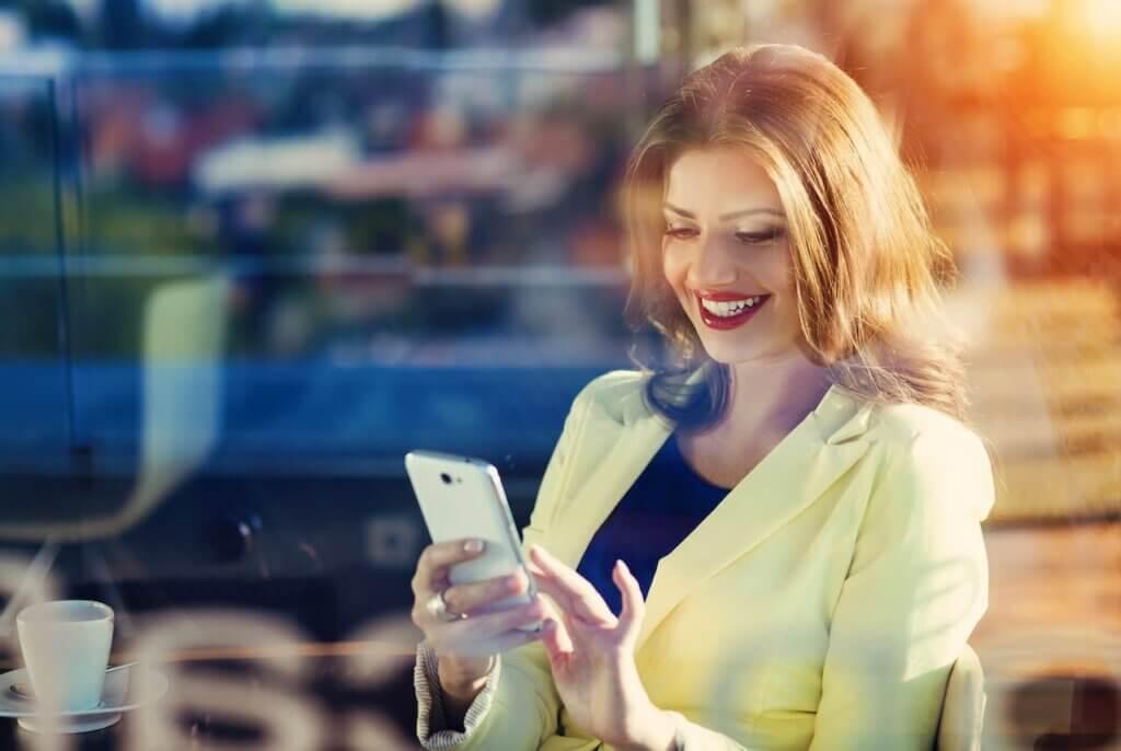 Femeie care comunică direct cu brandul preferat, prin intermediul SMS-ului