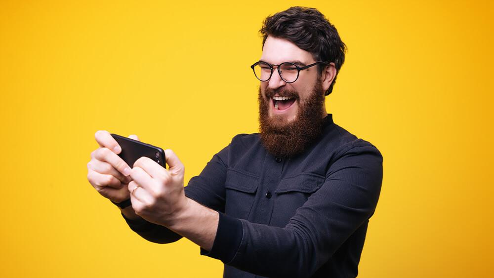 Bărbat care utilizează telefonul mobil pentru jocuri