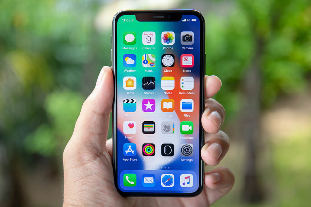 Mână care ține un telefon pe al cărui ecran se găsesc diverse aplicații mobile