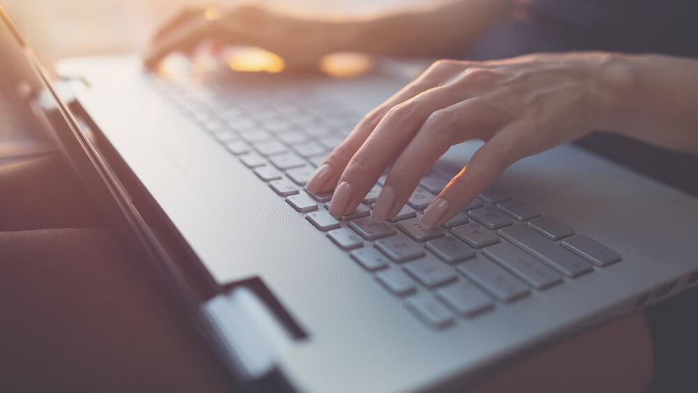 Femeie la laptop care compune mesaje declanșatoare