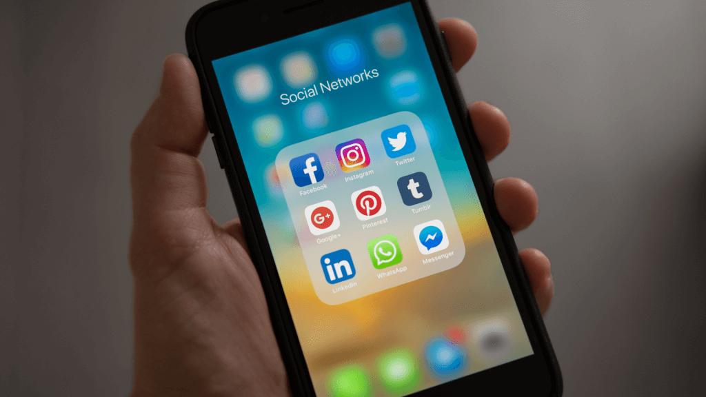 Telefon pe al cărui ecran sunt expuse simbolurile rețelelor sociale