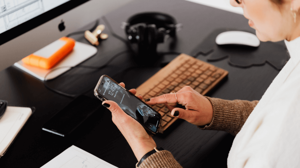 Femeie care verifică ora pe telefonul mobil