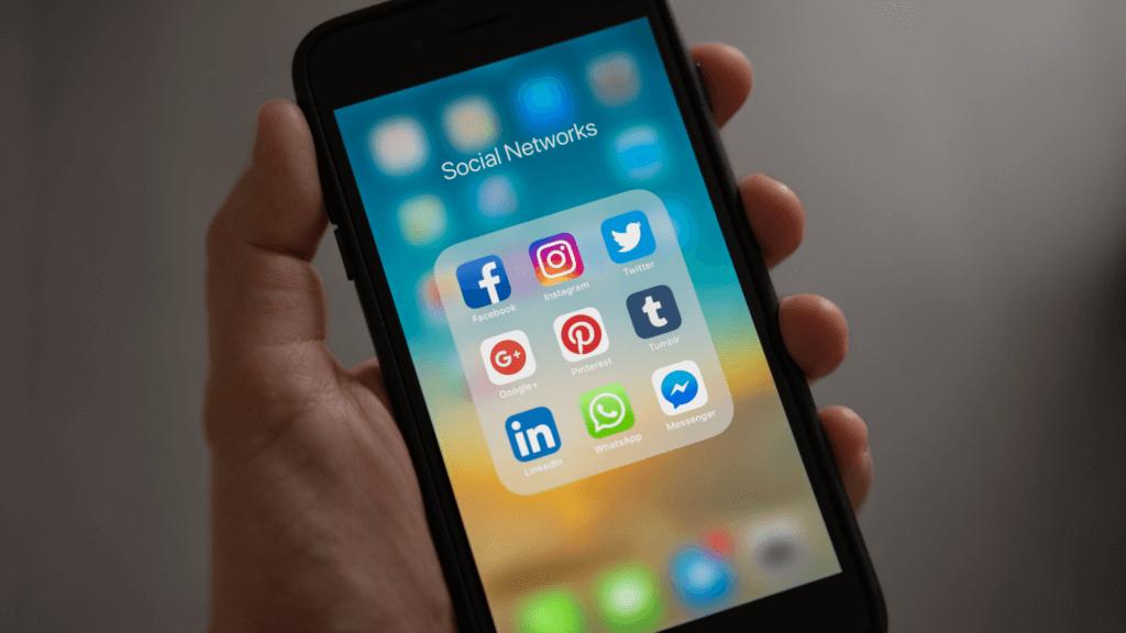 Telefon pe ecranul căruia apar icoanele rețelelor de socializare