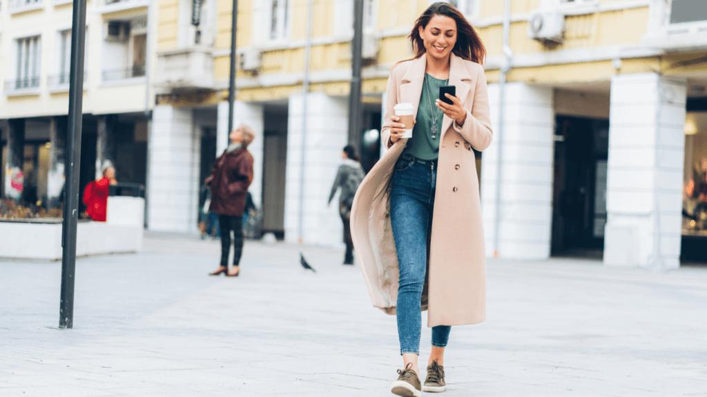 Fată care utilizează telefonul mobil pe stradă