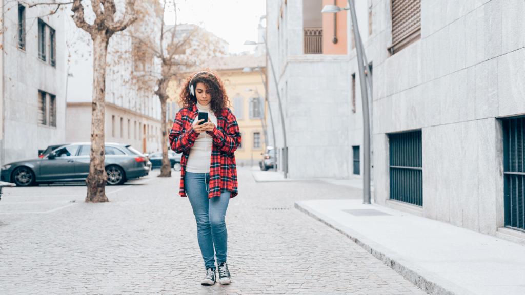 Fată care utilizează telefonul pe stradă