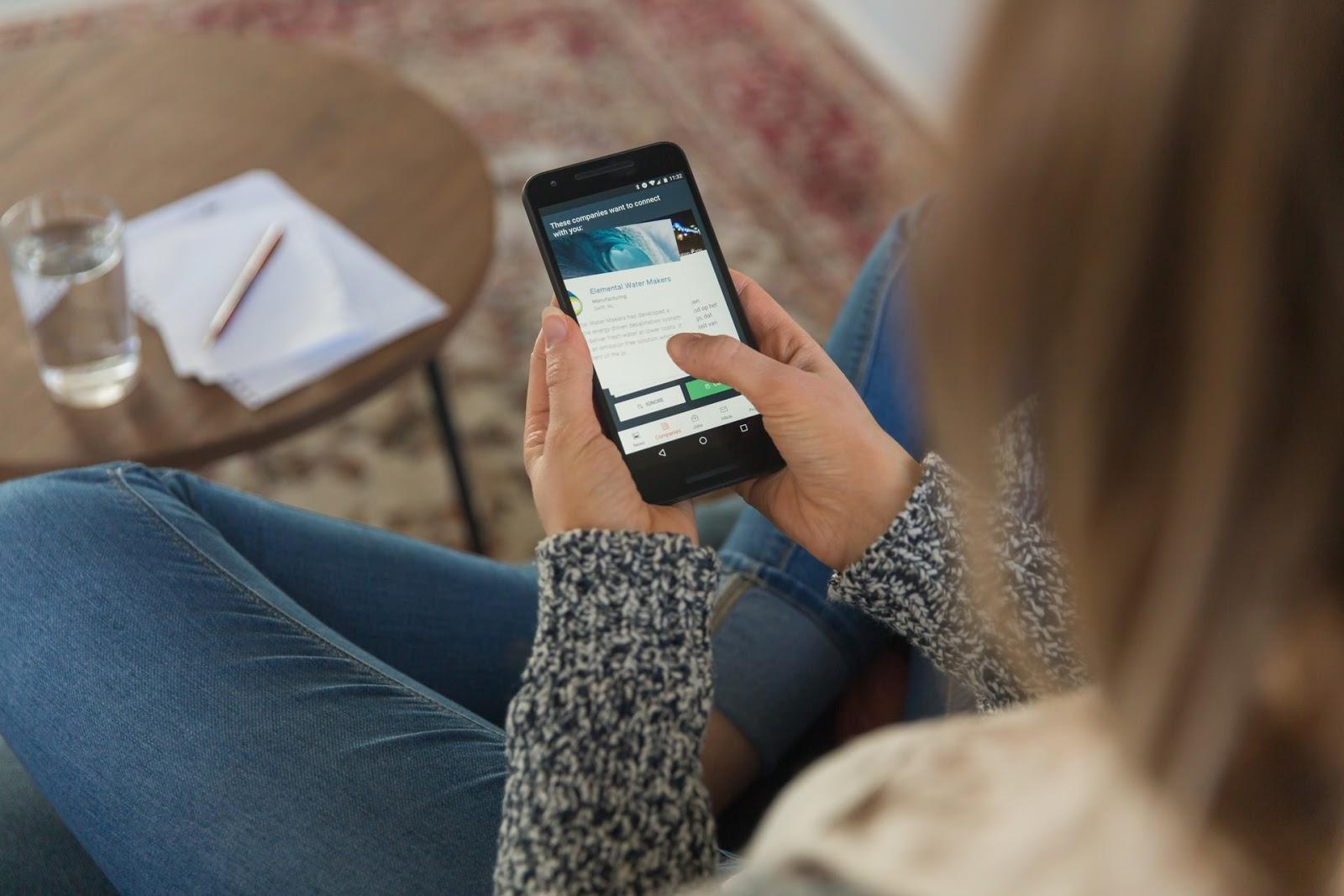 Tânără care citește mesajele personalizate primite pe telefonul mobil