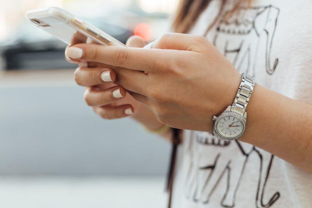 Tânără care utilizează telefonul mobil