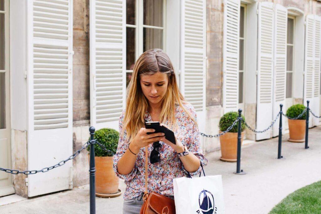 Femeie care utilizează telefonul pentru a-și verifica mesajele