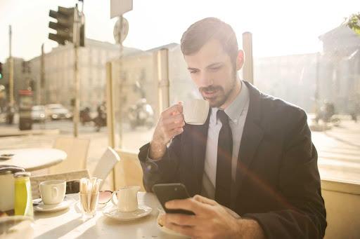 Barbat care utilizeaza telefonul mobil pentru a efectua o plata prin SMS
