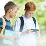 Copii care utilizează telefonul mobil în drum spre școală